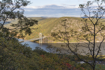 mountin: The Bear Mountain Bridge vignetted by dark trees from the Appalacian Trail in Bear Mountin State Park, New York.