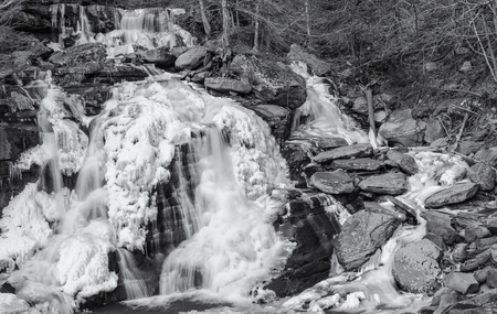 frozen creek: Half frozen Bastion Falls beside Route 23A on Lake Creek, about 12 miles downstream of Kaaterskill Falls in the Catskills Mountains of New York. (Black and White)