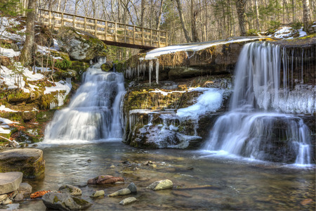 strata: Water falls gently over rocky strata at partially frozen West Kill Falls in the Catskills Mountains of New York.