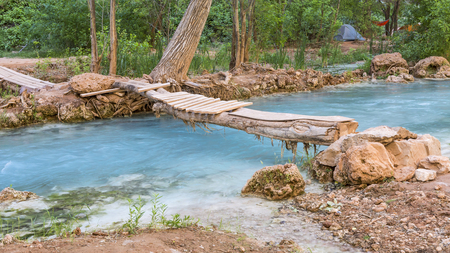 campground: A wooden footbridge crosses Havasu Creek in the campground on the Havasupai Indian Reservation in the Grand Canyon. Stock Photo