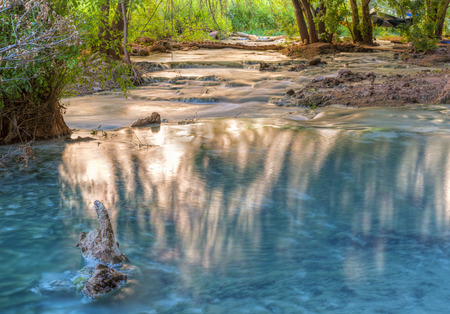 indian creek: Sunlight bounces off the far cliffs and lights up reflections in Havasu Creek on the Havasupai Indian Reservation in the Grand Canyon.