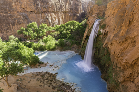 cataract falls: Havasu Falls plunges into a deep blue-green pool, with Cataract Canyon behind lit by the morning sun, on Havasupai Indian Reservation in the Grand Canyon.