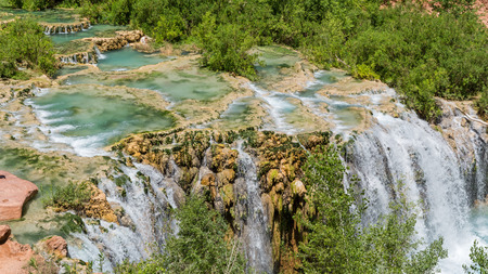 Water from Havasu Creek flows over travertine pools and rushes over Little Navajo Falls on the Havasupai Indian Reservation in the Grand Canyon.