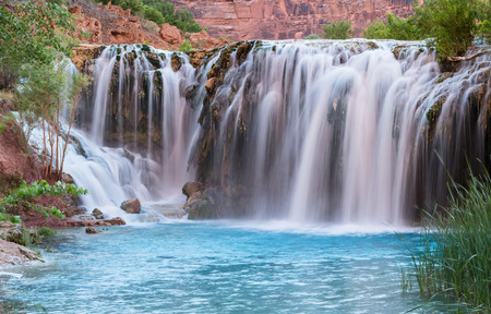 indian creek: Silly water flows over Little Navajo Falls into a turquoise pool on the Havasupai Indian Reservation in the Grand Canyon. Stock Photo