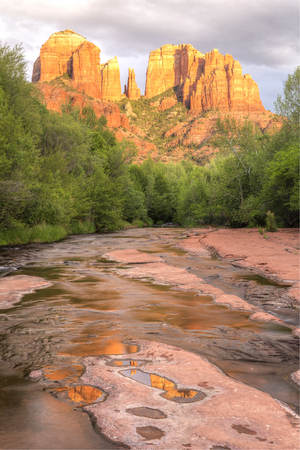 Cathedral Rock is reflected in puddles on the slickrock on Oak Creek in Red Rock Cross-Crescent Moon Park in Sedona, Arizona