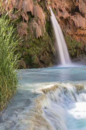 A travertine ledge below Havasu Falls where it plunges into a deep blue-green pool on the Havasupai Indian Reservation in the Grand Canyon.