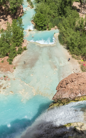 Havasu Creek plunges 100 feet over a travertine cliff  into a pure turquoise pool on the Havasupai Indian Reservation in the Grand Canyon. Stock Photo