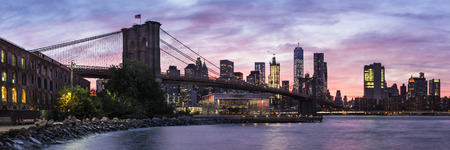 A colorful twilight view of the Brooklyn Bridge, Janes Carousel and the Manhattan skyline see from Empire Fulton Ferry Park in Brooklyn. NY Stock Photo