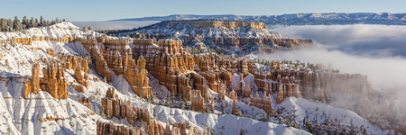 Panoramic image of fog and low hanging clouds partially cover snow-capped hoodoos Bryce Canyon National Park, Utah (Panorama) Stock Photo