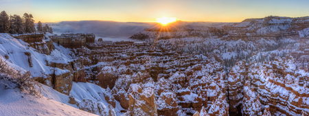The sun rises out of the a fog bank over the Silent City of snow shrouded hoodoos and Sunset Point in Bryce Canyon National Park, Utah