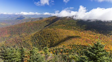 Cornell and Wittenburg Mountains shrouded in misty clouds, seen from a lookout on Slide Mountain during peak Autumn color in the Catskills Mountains of New York.