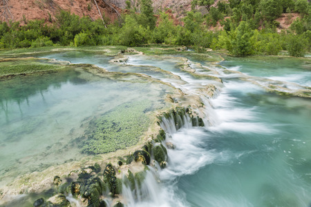 The crystal clear turquoise waters of Havasu Creek flow over travertine terraces forming pools in Havasupai Indian Reservation, Arizona.