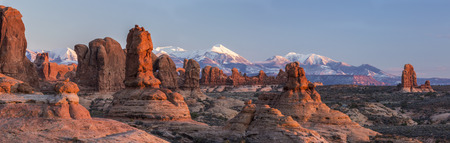 Warm late afternoon sunlight sidelights the rock formations in the Garden of Eden, with the Windows section behind in Arches National Park, Utah