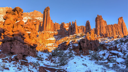 Rock fins rise above the a snowy canyon at the Fisher Towers rock formations near Moab, Utah