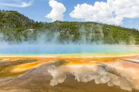 Clouds reflected in the the vivid rainbow colors of the Grand Prismatic Spring in Yellowstone National Park, Wyoming Stock Photo
