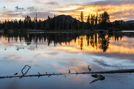 A colorful summer sunrise reflected in ripples in glassy Sprague Lake in Rocky Mountain Naitonal Park, Colorado