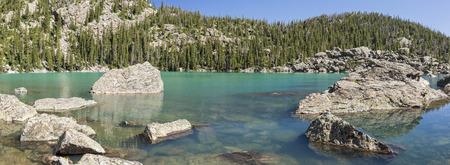 Blue sky reflects in the vivid green waters of Lake Haiyaha in Rocky Mountain National Park, Colorado