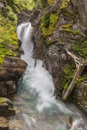 Cataract Creek plunges through a gorge at Hidden Falls near Grinnell Lake in Glacier National Park, Montana Stock Photo