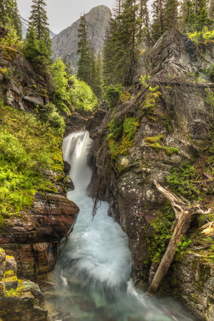 Cataract Creek plunges through a gorge at Hidden Falls below Angel Wing Mountain in Glacier National Park, Montana