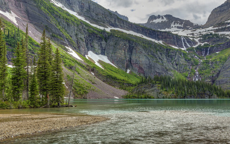 north cascade national park: A waterfall flows from Grinnell Glacier into turquoise Grinnell Lake in Glacier National Park, Montana