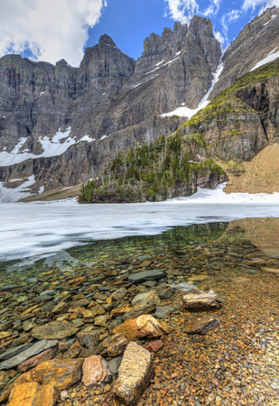 Iceberg Notch and the Ptarmigan Wall towers 3000 feet above mostly frozen Iceberg Lake in June in Glacier National Park, Montana