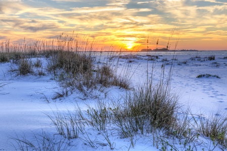 A colorful sunset over the seaoats and dunes on Fort Pickens Beach in the Gulf Islands National Seashore, Florida.