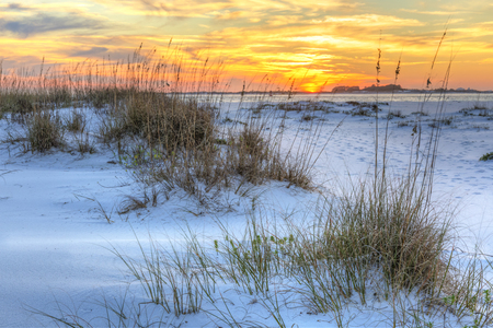 A colorful sunset over the seaoats and dunes on Fort Pickens Beach in the Gulf Islands National Seashore, Florida. Stock Photo