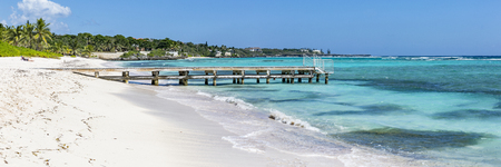 A wooden pier juts into the turquoise waters of the Carribbean on Spotts Beach in Savannah, Grand Cayman, Cayman Islands