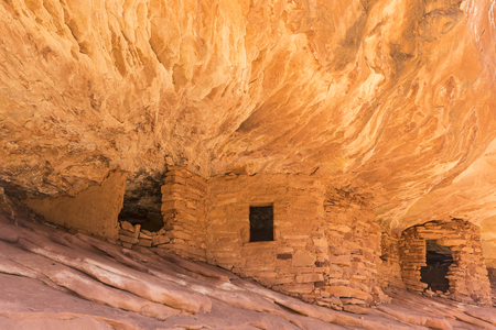 Puebloan ruins under  a cliff in Mule Canyon in the Cedar Mesa Plateau in Bears Ears National Monument in Utah look like the ancient stone granaries and dwellings are on fire. Stock Photo