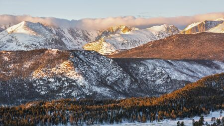 The Continental Divide crowned with a line of clouds in the early morning sun in Rocky Mountain National Park, Colorado.