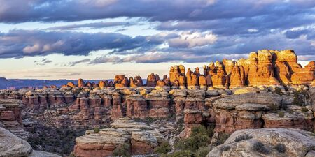 Moody clouds above colorful golden lit needles in Elephant Canyon in the Needles District of Canyonlands National Park. Stock Photo