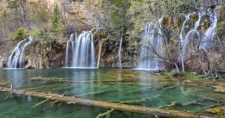 Warm morning sun reflects off the cliffs above the Hanging Lake waterfalls in Dead Horse Canyon near Glenwood Springs, Colorado. Stock Photo