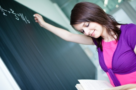 pretty young college student writing on the chalkboard/blackboard during a math class  Stock Photo - 9692143