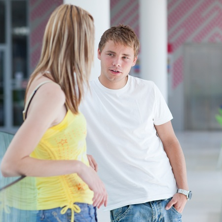 two college students talking/flirting on campus (shallow DOF, color toned image) Stock Photo - 9696899