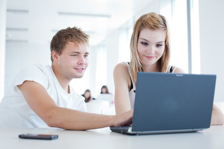 two college students having fun studying together, using a laptop computer (shallow DOF, color toned image) Stock Photo - 9697419