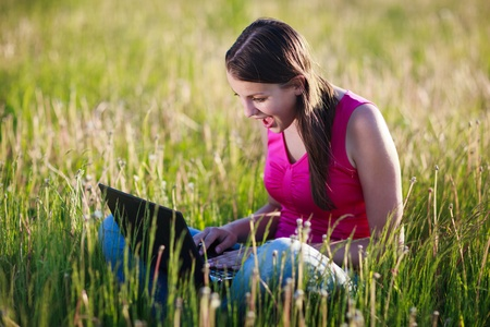 pretty , young woman using her laptop computer outdoors in the middle of a lovely field - staring at the screen in amazement Stock Photo - 9771886