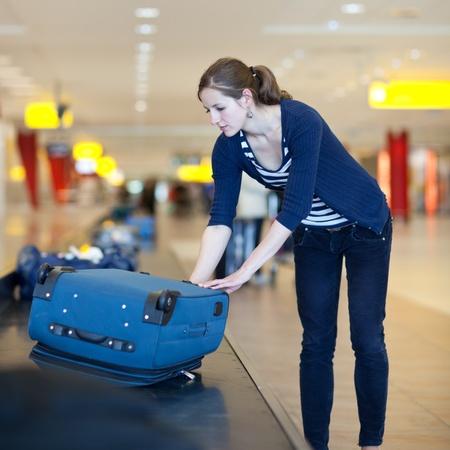 bagage: De retrait des bagages � l'a�roport - jolie jeune femme prenant sa valise hors du carrousel � bagages