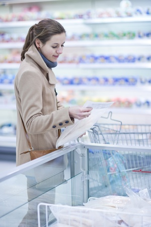 pretty young woman buying groceries in a supermarket/mall/grocery store (color toned image; shallow DOF) Stock Photo - 9697451