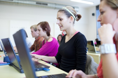 young, pretty female college student sitting in a classroom full of students during class (shallow DOF) photo