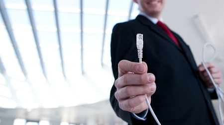 business concept - young businessman holding a cable - stressing the importance of fast and reliable internet connection for a business Stock Photo - 9786287