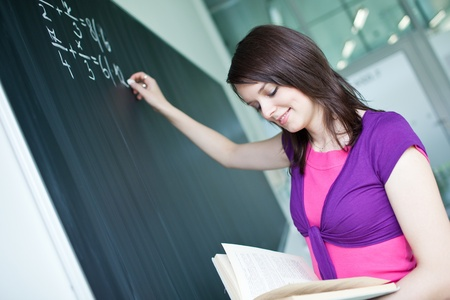 pretty young college student writing on the chalkboard/blackboard during a math class Stock Photo - 9697896