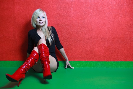 Beautiful young female photo model wearing high red boots, posing in front of a red wall photo