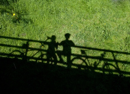 cycling related background - two mountain bikers silhouettes during a halt on a bridge photo
