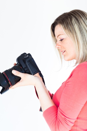 pretty female photographer with her digital camera (color toned image; shallow DOF) photo