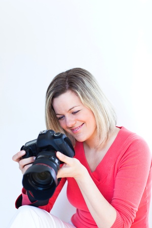 pretty female photographer with her digital camera (color toned image; shallow DOF) Stock Photo - 9795419