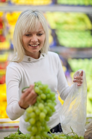 Beautiful young woman shopping for fruits and vegetables in produce department of a grocery store/supermarket Stock Photo - 9795411