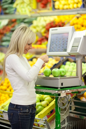 Beautiful young woman shopping for fruits and vegetables in produce department of a grocery store/supermarket (shallow DOF) Stock Photo - 9792344