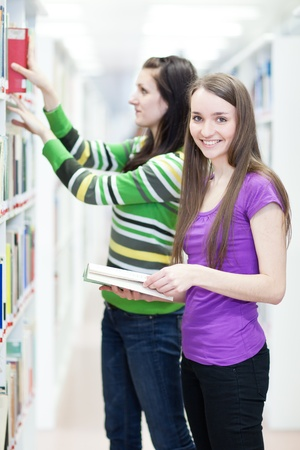 two pretty, young college students in a library (shallow DOF; color toned image) Stock Photo - 9792265