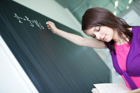 pretty young college student writing on the chalkboard/blackboard during a math class Stock Photo - 9792549
