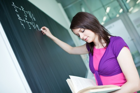 pretty young college student writing on the chalkboard/blackboard during a math class Stock Photo - 9792552